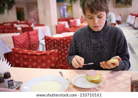 Boy sitting at the table in the restaurant and spreading butter on bread - stock photo
