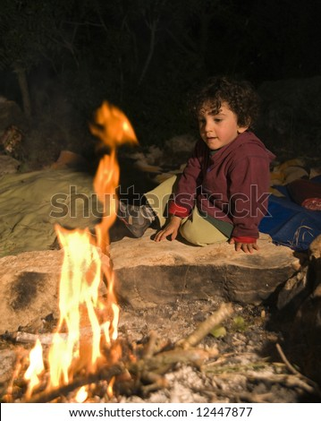 boy sitting by the fire in a camp - stock photo