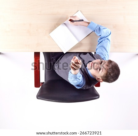 Boy sitting in a chair at the office table. Top view