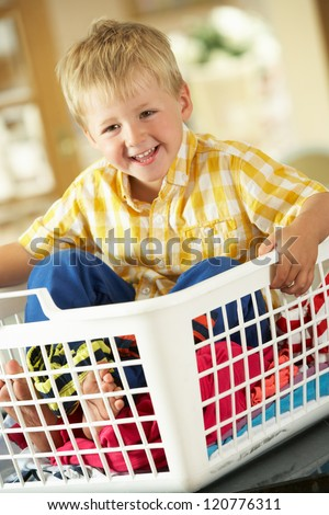 Boy Sitting In Basket Sorting Laundry On Kitchen Counter