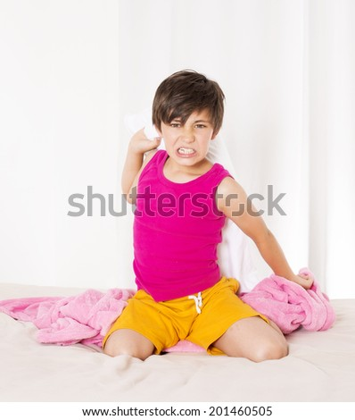 boy sitting in bed with pillow in his hand and being angry