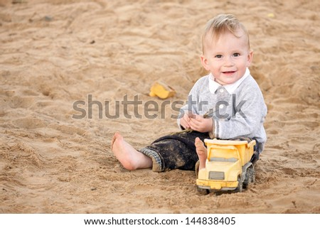 Boy sitting in sandpit and smiling - stock photo