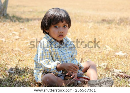 Boy sitting in the grass at summer. - stock photo