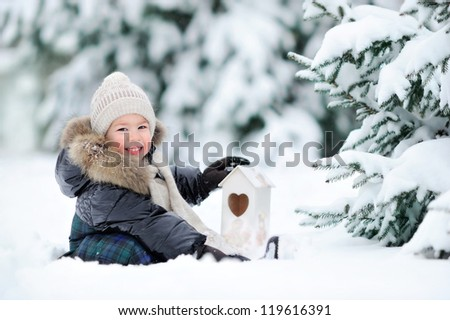Boy sitting in the snow. Baby near the Christmas tree in the winter. Happy baby.