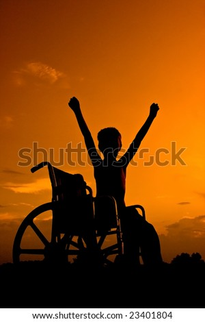 Boy sitting in wheel chair at sunset signaling victory - stock photo