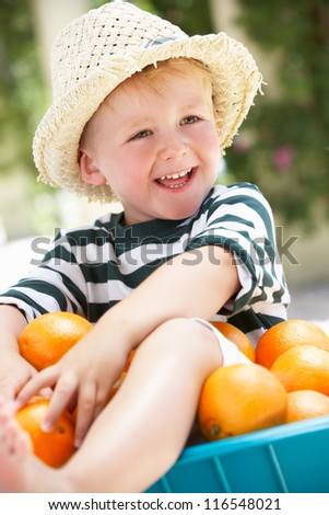 Boy Sitting In Wheelbarrow Filled With Oranges - stock photo