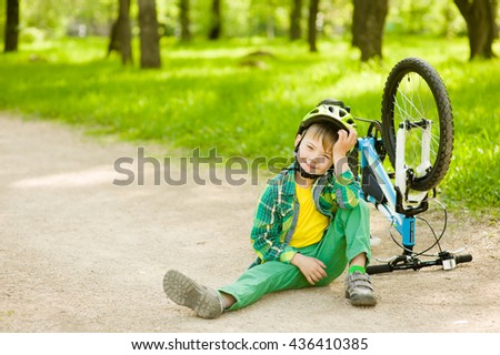 Boy sitting near a broken bicycle
