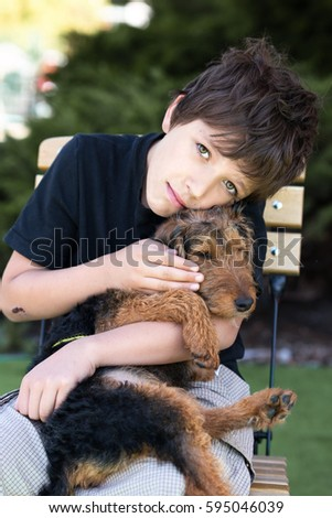 Boy sitting on a chair and hugging close a little puppy, dog - welsh terrier. Love portrait. Childhood with pets and animals.