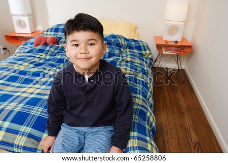 Boy sitting on bed - stock photo