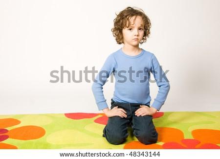 Boy sitting on colorful carpet - stock photo