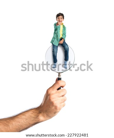 boy sitting on magnifying glass - stock photo