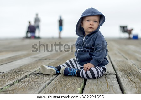 boy sitting on old wooden pier