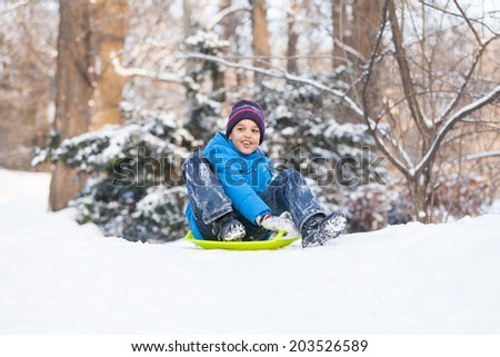 boy sitting on sledges and sliding down. child playing in park on snow in winter - stock photo