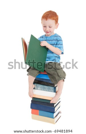Boy sitting on stack of books and reading. Isolated on white.