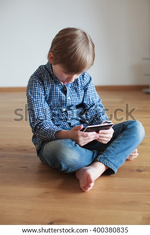 Boy sitting on the floor and reading electronic book