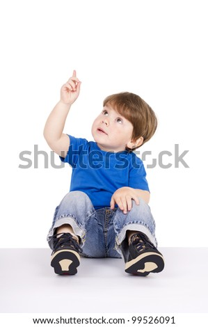 Boy sitting on the floor pointing upwards. Isolated on white.