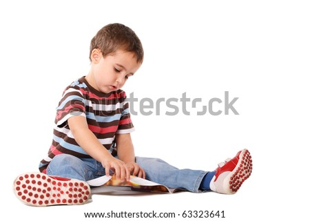 Boy sitting on the floor reading magazine isolated on white - stock photo