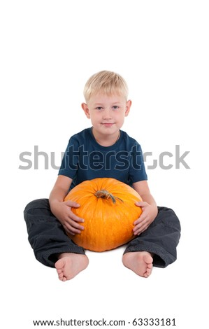 Boy sitting on the floor with a big pumkin in his legs - stock photo