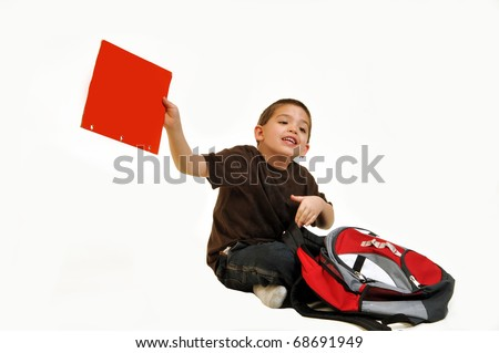 Boy, sitting on the floor with school backpack holding a red folder that shows product message. - stock photo