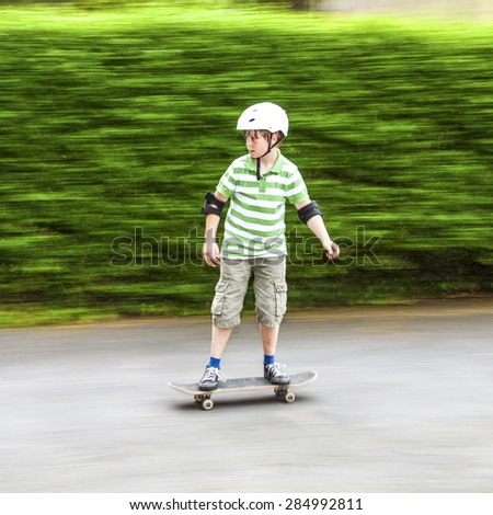boy skating with speed with green blurred background - stock photo