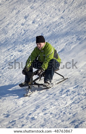 Boy Sledding Down Snowy Hill In Winter - stock photo
