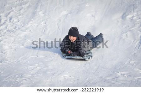 Boy sledding in the snow - stock photo