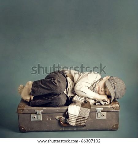 boy sleeping on a suitcase - stock photo