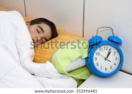 boy sleeping with alarm clock - stock photo
