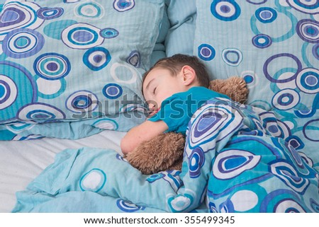 boy sleeping  with cat  on the bed   - stock photo