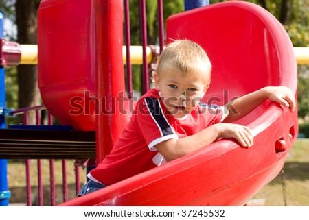 Boy slides down a spiral slide - stock photo
