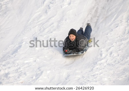 Boy sliding down the hill - stock photo