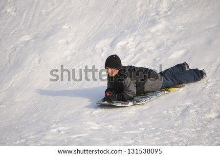 Boy sliding down the hill on the sled - stock photo