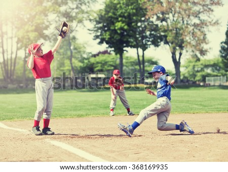 Boy sliding into base during a baseball game with Instagram style filter, focus is on catcher. - stock photo