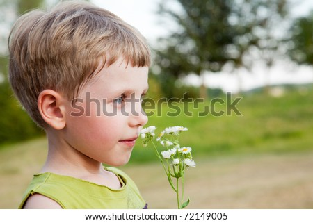 Boy smelling wild flowers outdoors - stock photo