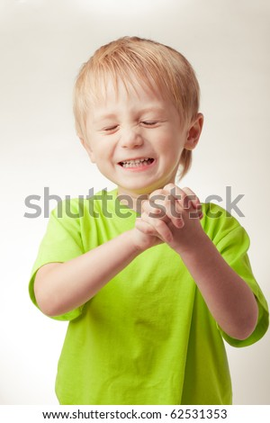 Boy smiled, his eyes shut, hands folded, on a gray background - stock photo