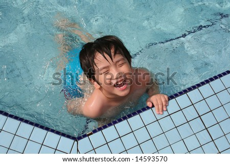 Boy smiling and having fun in the pool - stock photo
