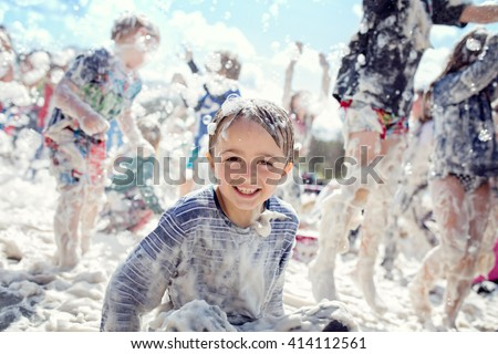 Boy smiling and laughing covered in soap suds at a summer foam party - stock photo