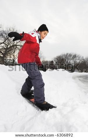 Boy snowboarding in snow. - stock photo