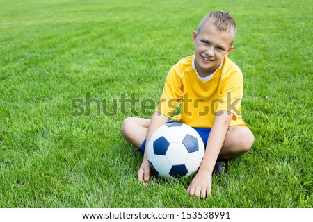 Boy soccer player with the ball is sitting on the football field.