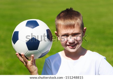 Boy soccer player with the ball on the football field.