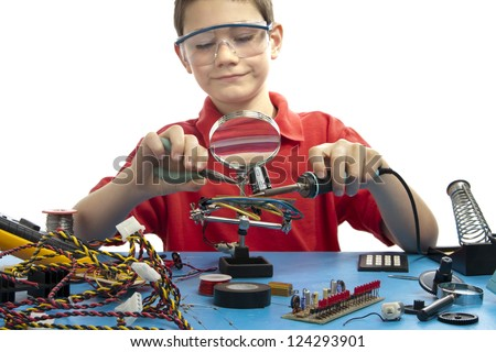 Boy soldering a component onto a printed circuit board while wearing safety glasses and red shirt.  He is surrounded with miscellaneous electrical parts. - stock photo