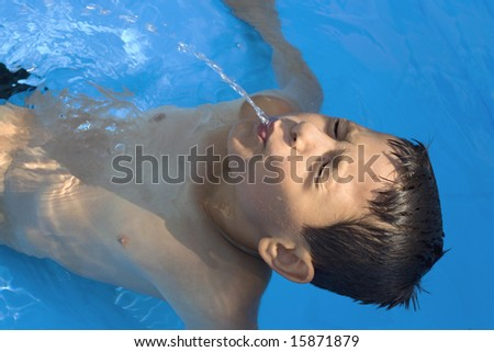 Boy squirt water  in the pool - stock photo