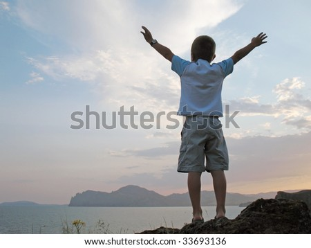 boy stand on mountain top with hands up on sunset sky - stock photo