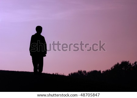 Boy standing alone on a hill dark silhouette over evening sky