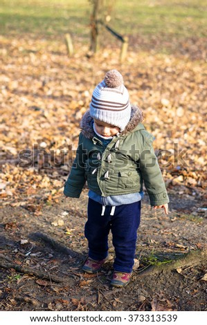 Boy standing by leaves at a park - stock photo