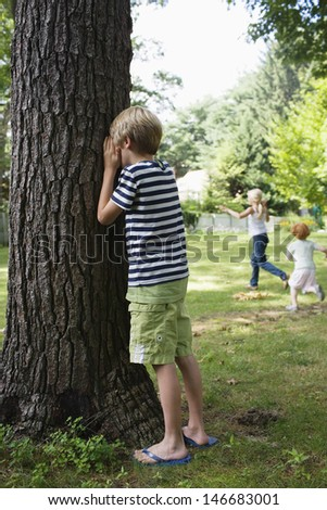 Boy standing by tree with eyes covered as children running in the background - stock photo