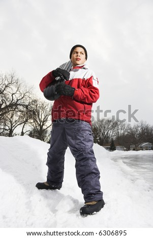 Boy standing holding snowboard in snow. - stock photo