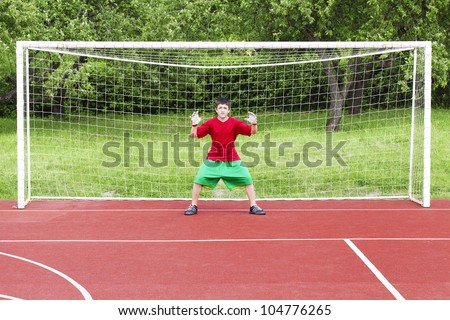 Boy standing in football goal - stock photo