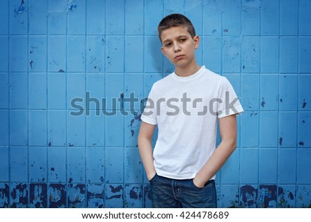 Boy standing in front of blue background