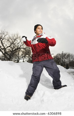 Boy standing in snow throwing snowball. - stock photo
